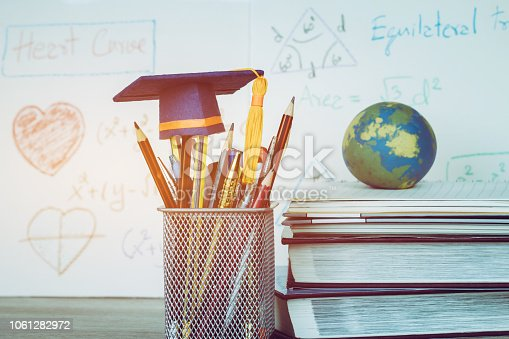 959387240 istock photo Education Graduate study concept: Graduation hat on pencils with formula arithmetic equation graph on near global model at university classroom. Ideas for knowledge learning success, Back to School 1061282972