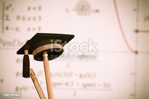 959387240 istock photo Education Graduate study concept: Graduation hat on pencils with formula arithmetic equation graph on projecter screen at university classroom. Ideas for knowledge learning success and Back to School 1062761942