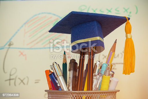 959387240 istock photo Education Graduate study concept: Graduation hat on pencils with formula arithmetic equation graph on projecter screen at university classroom. Ideas for knowledge learning success and Back to School 972364306