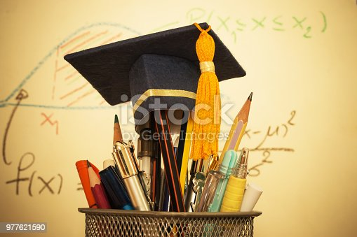 959387240 istock photo Education Graduate study concept: Graduation hat on pencils with formula arithmetic equation graph on projecter screen at university classroom. Ideas for knowledge learning success and Back to School 977621590
