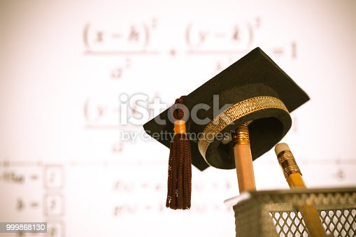 959387240 istock photo Education Graduate study concept: Graduation hat on pencils with formula arithmetic equation graph on projecter screen at university classroom. Ideas for knowledge learning success and Back to School 999868130