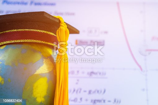 959387240 istock photo Education Graduate study international concept: Graduation cap on top Earth globe model map with formula equation graph on screen classroom. Ideas for knowledge learning success, Back to School 1056832404