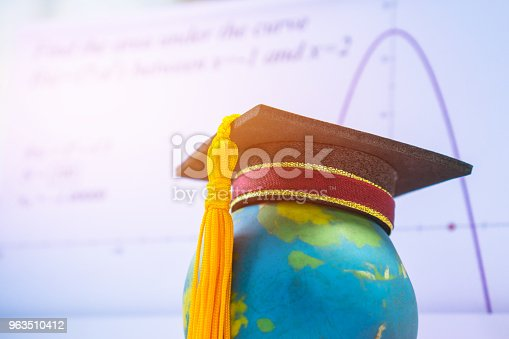 959387240 istock photo Education Graduate study international concept: Graduation cap on top Earth globe model map with formula equation graph on screen classroom. Ideas for knowledge learning success, Back to School 963510412