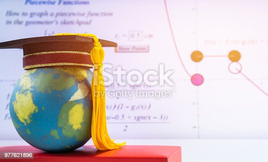 959387240 istock photo Education Graduate study international concept: Graduation cap on top Earth globe model map with formula equation graph on screen classroom. Ideas for knowledge learning success, Back to School 977621896
