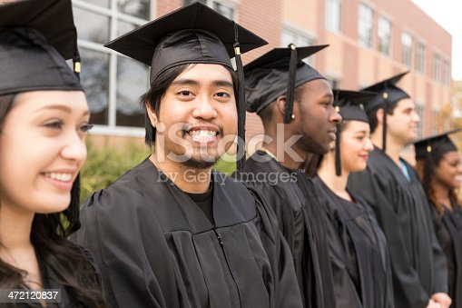 istock Education: Graduates stand in row on college campus. 472120837