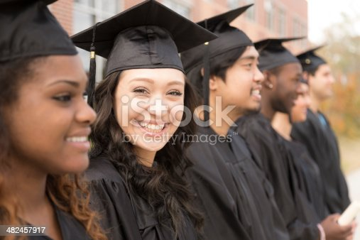 istock Education: Graduates stand in row on college campus. 482457917