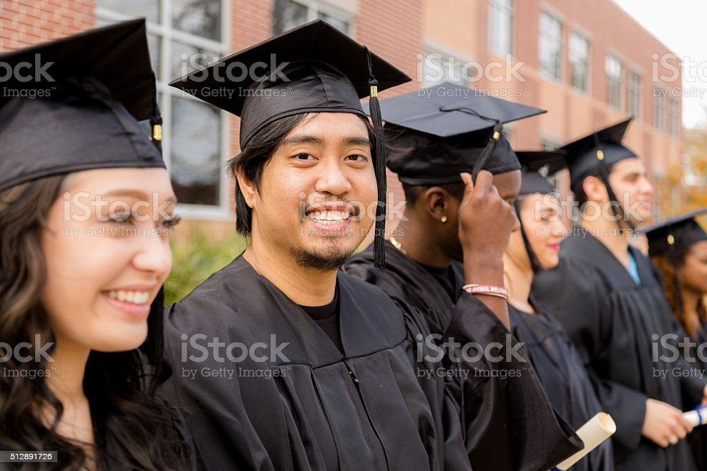 Education: Graduates stand in row on college campus. stock photo