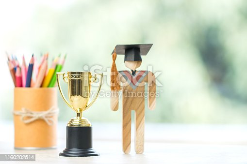 865186916 istock photo Education graduation in achievement success concept: Students university models with golden trophy winner with pencils, intelligence for management study competition leadership and inspiration in life 1160202514