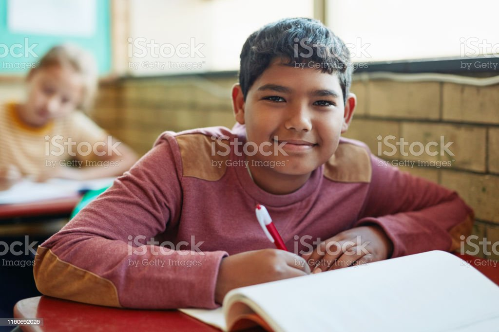 Shot of a young boy doing schoolwork in a classroom