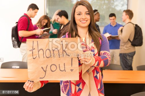istock Education: Latin descent college student holds 'Thank you' sign. Classroom. 511311156