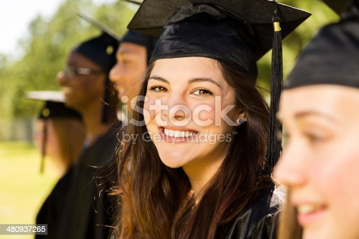istock Education: Latin girl and friends at graduation. Cap, gown. 480937265