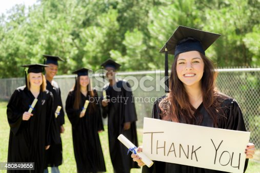 istock Education: Latin girl holds 'Thank You' sign after graduation. Friends. 480849655