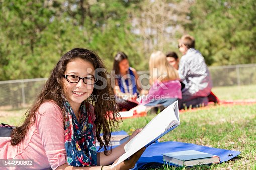 istock Education: Latin pre-teenage girl studies at local park. Friends background. 544990802