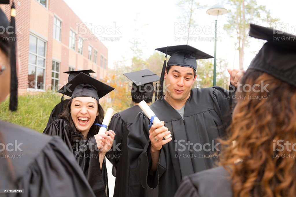 Education: Male, female graduates and friends on college campus. stock photo