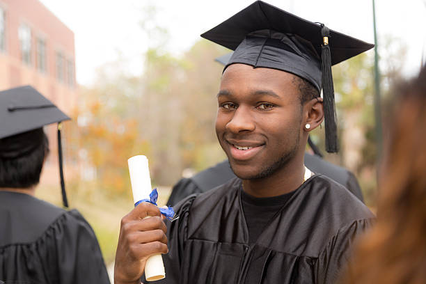 Education: Male graduate and friends on college campus. stock photo