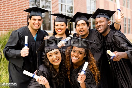 istock Education: Multi-ethnic friends excitedly hold diplomas after college graduation. 482362583