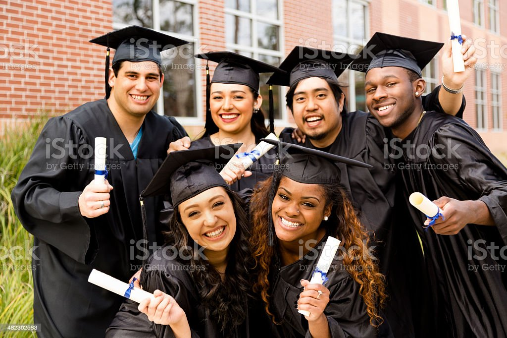 Education: Multi-ethnic friends excitedly hold diplomas after college graduation. stock photo