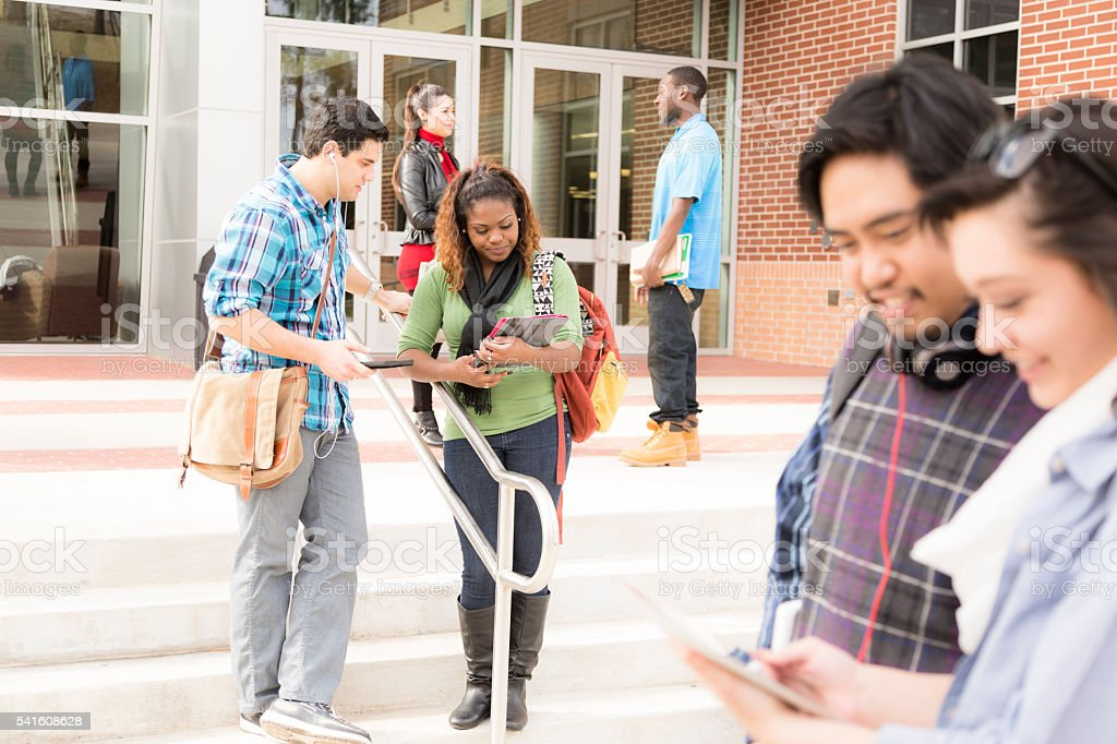 Diverse group of college students talk outside school building...