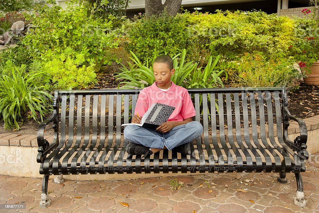 Education: One elementary student waiting on a bench. royalty-free stock photo