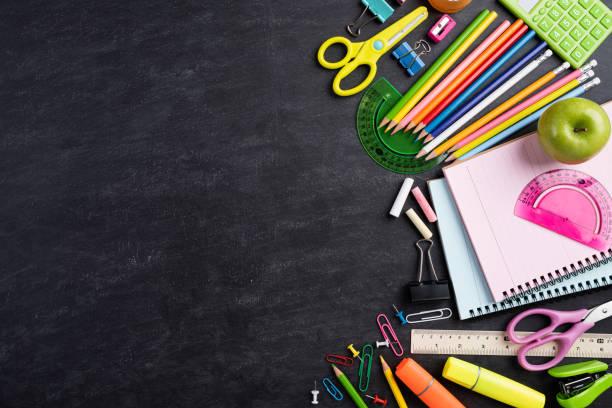 Bildung oder zurück zur Schule Konzept. Top-Ansicht der bunten Schulbedarf mit Büchern, Farbstifte, Taschenrechner, Stift Schneider Clips und grünen Apfel auf Tafel Hintergrund. Flach liegen. – Foto