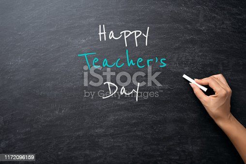 977488078 istock photo Education or back to school Concept. Woman hand holding chalk with Happy Teacher's Day text over chalkboard background. 1172096159