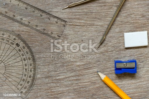 1060723604istockphoto Education or draft tool on wood background (pencil, sharpener, set square, ruler, compass circle) 1043658614
