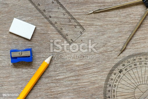 1060723604istockphoto Education or draft tool on wood background (pencil, sharpener, set square, ruler, compass circle) 992910202