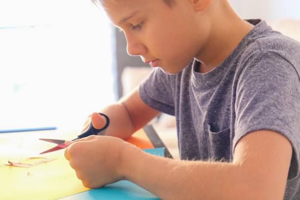 Bildung, Papierhandwerk für Kinder. Kind schneidet farbiges Papier mit Schere und machen Grußkarte zu Hause – Foto