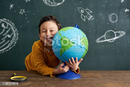 6-7 years old cute child standing front of blackboard with world globe