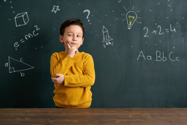 Education 6-7 years old cute child standing front of blackboard 6 7 years stock pictures, royalty-free photos & images