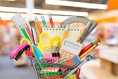 Shopping cart with colorful school stationery, back to school background