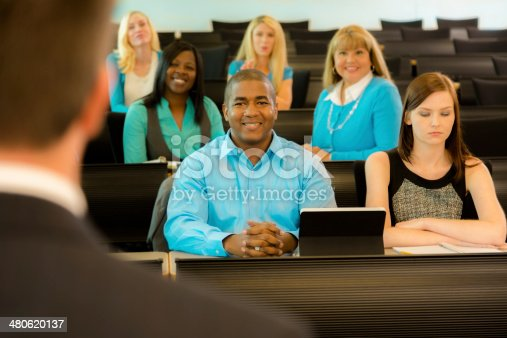 istock Education: Professor with mixed-age college students in lecture hall. 480620137