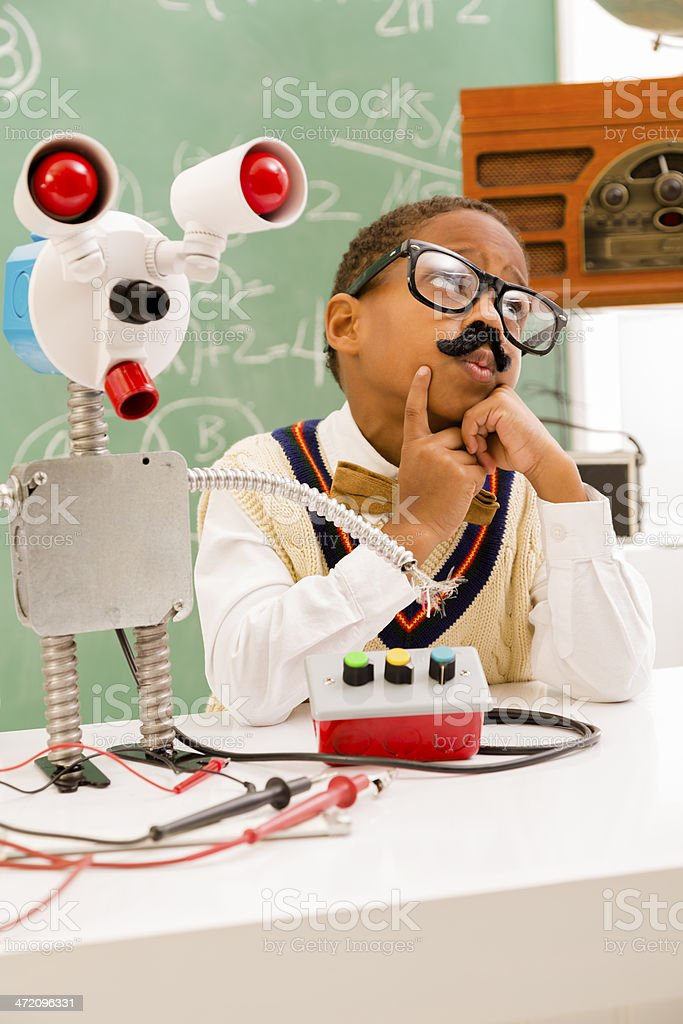 Education:  Retro revival boy making robot in science lab. stock photo