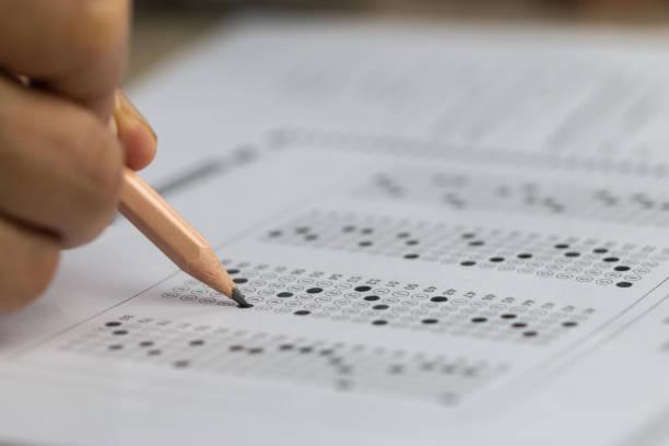 교육 학교 테스트 개념: 손 학생 들고 연필 시험 시험에 대 한 답변 시트를 작성 또는 운동에 대 한 입학 시험을 채우기 위한 연습 여러 탄소 종이 컴퓨터 대학 교실에서 - 일과 뉴스 사진 이미지