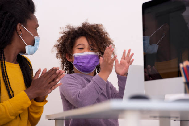 Education success despite the epidemic! A teacher woman and 6 years old elementary school girl cheering clapping hands, looking at the computer's screen. They are both wearing surgical masks because of the Coronavirus. despite stock pictures, royalty-free photos & images