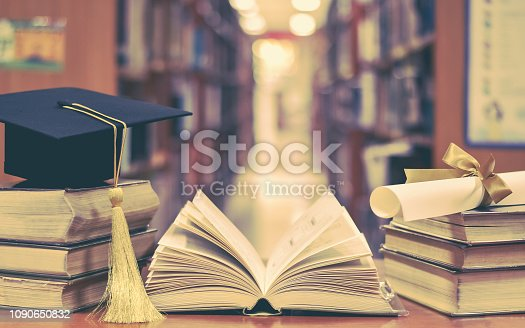 istock Education success with graduation hat, academic cap, mortarboard, and degree certificate on books and textbooks in class or library study room 1090650832