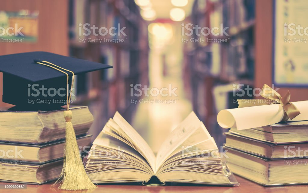 Education success with graduation hat, academic cap, mortarboard, and degree certificate on books and textbooks in class or library study room stock photo