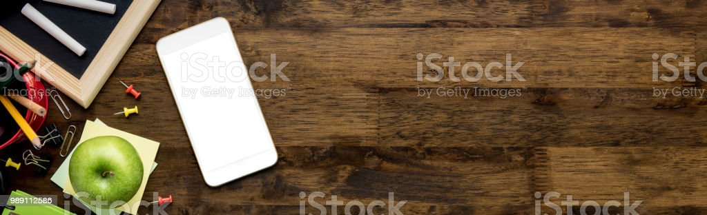 Education supplies with blank screen mobile phone on wooden table background stock photo