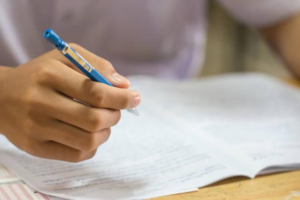 bildungsprüfungskonzept: hands asian students thai uniform holding pen for testing prüfungen writing answer sheet oder exercise for abfüllen prüfungspapier auf reihenholztisch im klassenzimmer in der high school - multiple intelligenz umfrage stock-fotos und bilder