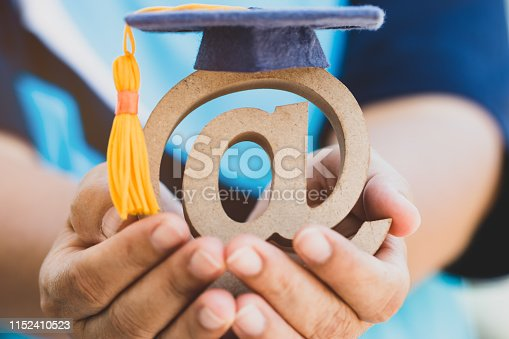 istock Education University of Online Learning in abroad educational concept: Graduation cap on email address symbol in student hand. Idea communication international school can learn by internet technology 1152410523