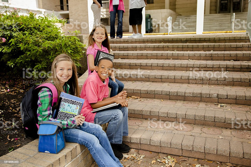 Education:  Young elementary age students on school steps. stock photo