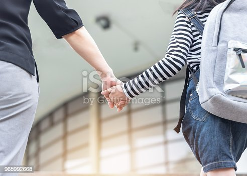 989255070istockphoto Educational Back to school or bring kid to work concept with elementary student girl carrying backpacks holding parent woman or mother's hand walking up school office building going to class 965992668