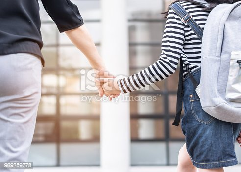 989255070istockphoto Educational Back to school or bring kid to work concept with elementary student girl carrying backpacks holding parent woman or mother's hand walking up school office building going to class 969259778