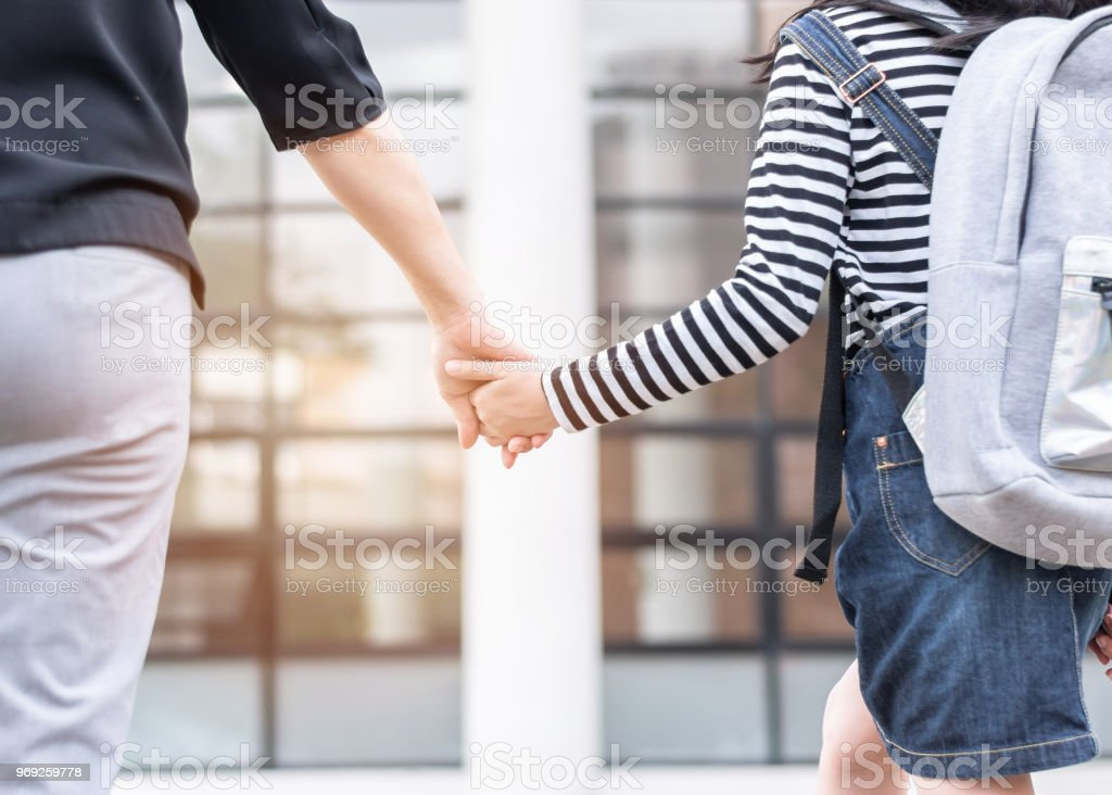 Respaldo educativo a la escuela o llevar niños para trabajar el concepto con chica estudiante elemental llevar mochilas con mujer de padre o de la mano de madre caminando hasta el edificio de la oficina de la escuela va a clase - foto de stock