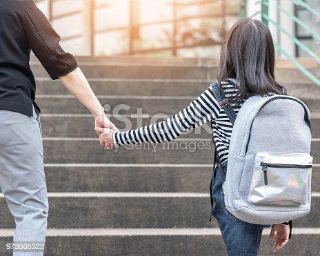 989255070istockphoto Educational Back to school or bring kid to work concept with elementary student girl carrying backpacks holding parent woman or mother's hand walking up school office od admission building going to class 973565322