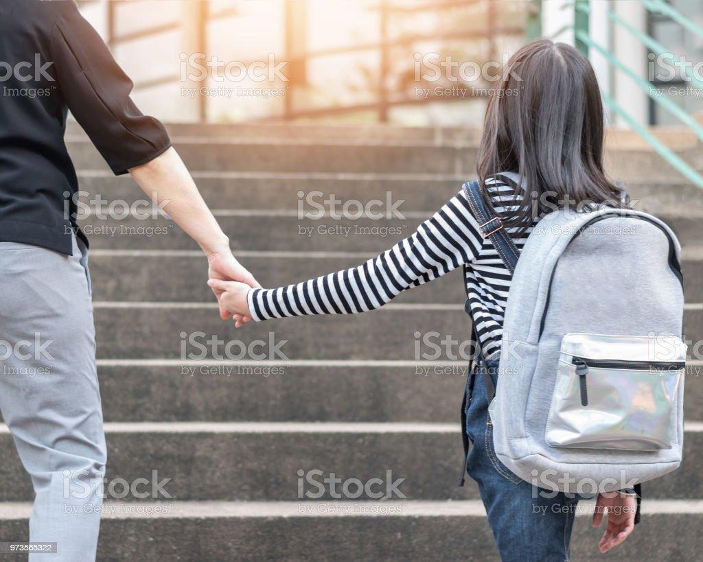 Respaldo educativo a la escuela o llevar niños para trabajar el concepto con chica estudiante elemental llevar mochilas con padres mujer o mano de la madre subiendo escuela od admisión edificio va a clase - foto de stock