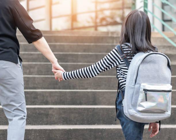 Pädagogische zurück zur Schule oder bringen Kind Konzept mit elementaren Studentin tragen Rucksäcke halten Eltern Frau oder Mutter die Hand zu Fuß hinauf Schule Od Eintritt Bürogebäude zum Unterricht zu gehen zu arbeiten – Foto