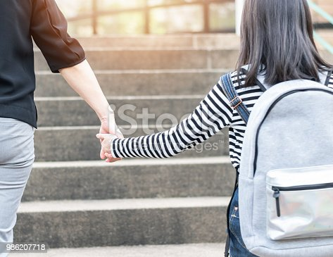 989255070istockphoto Educational Back to school or bring kid to work concept with elementary student girl carrying backpacks holding parent woman or mother's hand walking up school office building going to class 986207718
