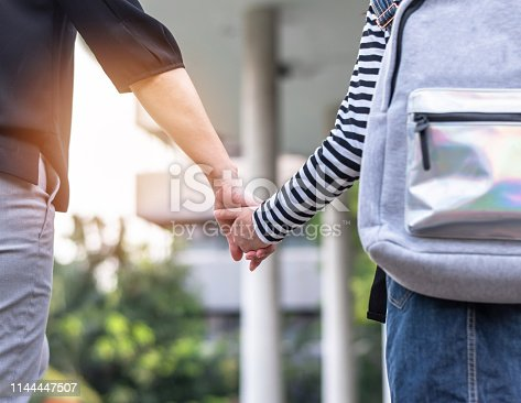 istock Educational back to school, parent's day, bring kid to work concept with elementary student girl carrying backpack holding woman or mother's hand walking up admission office building going to class 1144447507