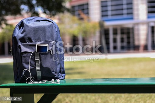 istock Educational objects on empty bench in front of school. 1010110240